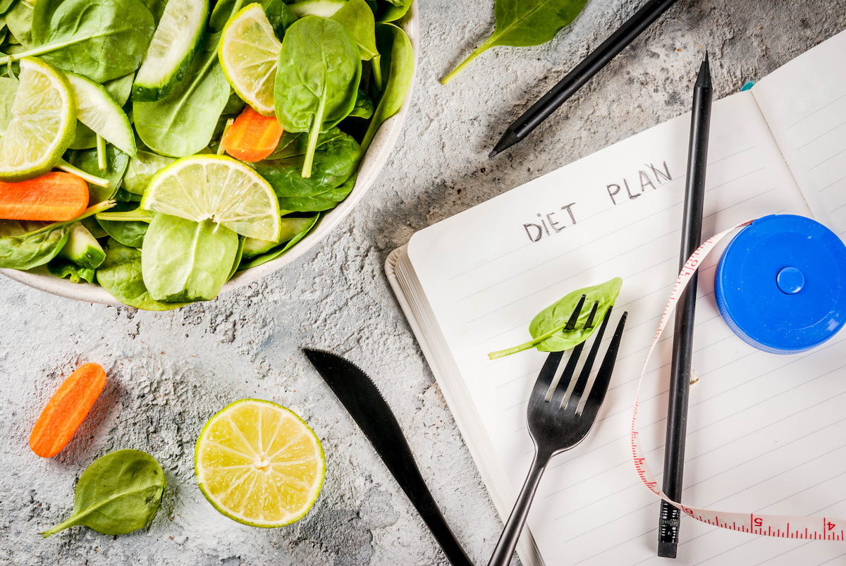 Diet plan weight lose concept, fresh vegetable salad with fork, knife, note pad,  grey stone table copy space top view